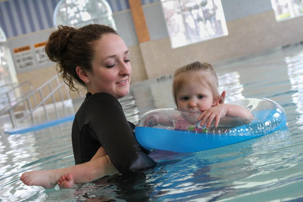 A young toddler and her physical therapist in a swimming pool.