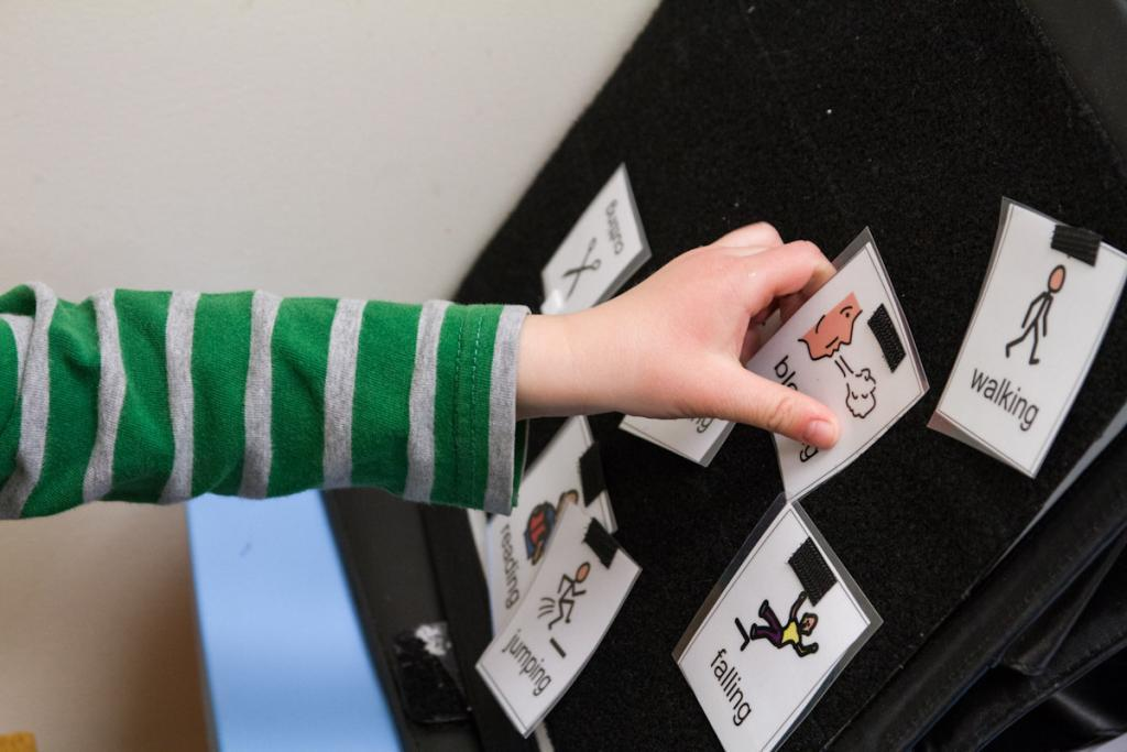 A child playing with flashcards as part of a speech therapy regimen.