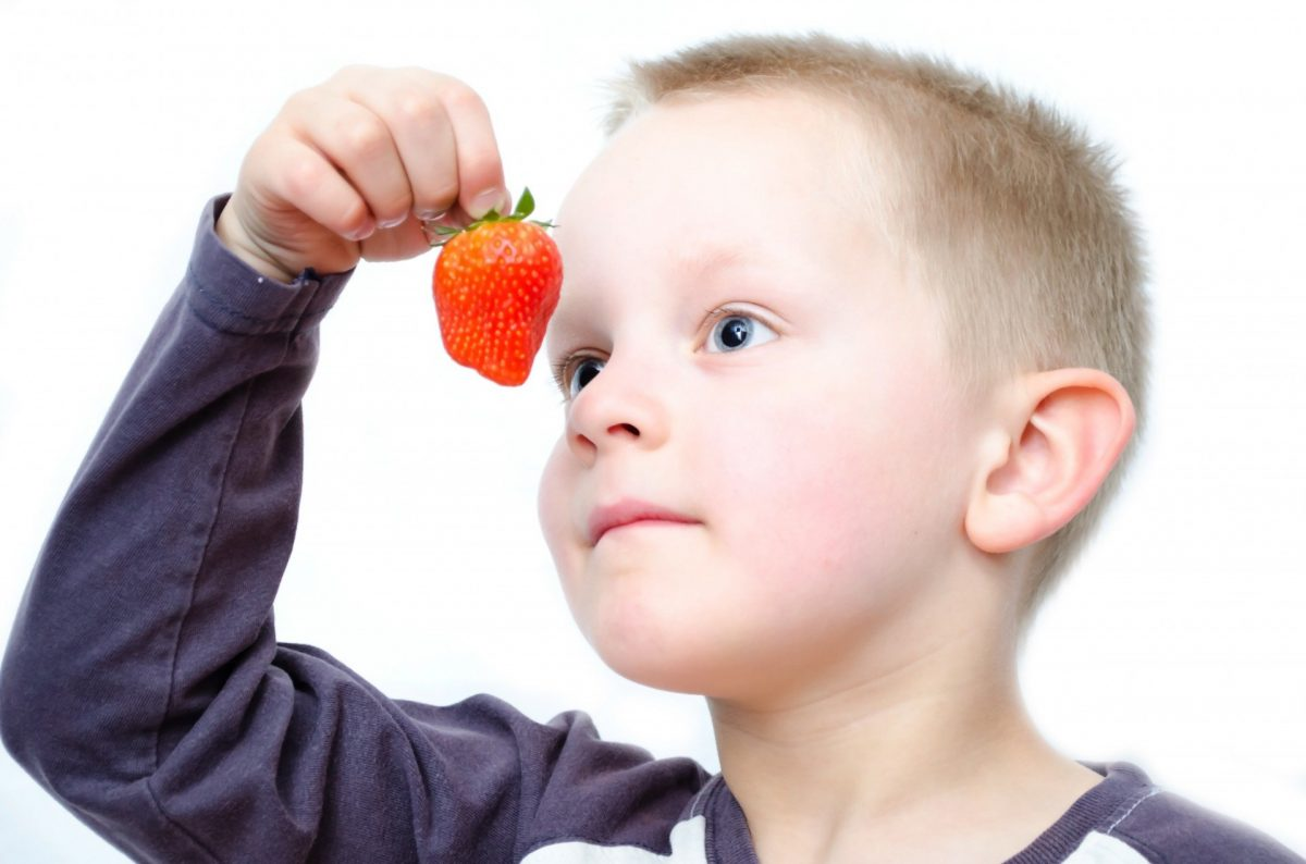 A child holding a strawberry in front of his face.