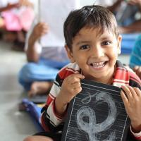 A young boy smiling with a chalkboard in a classroom.
