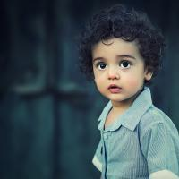 a young child with curly hair and a blue shirt