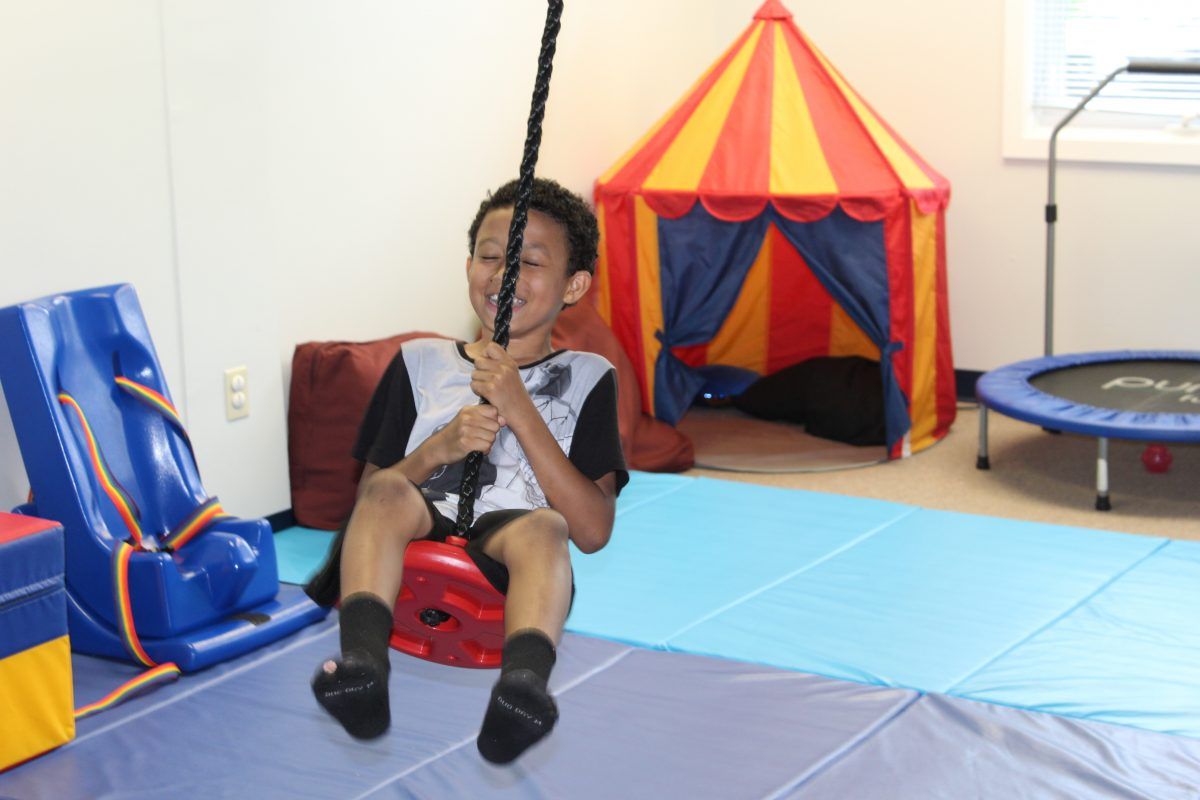 child on swing in physical therapy center