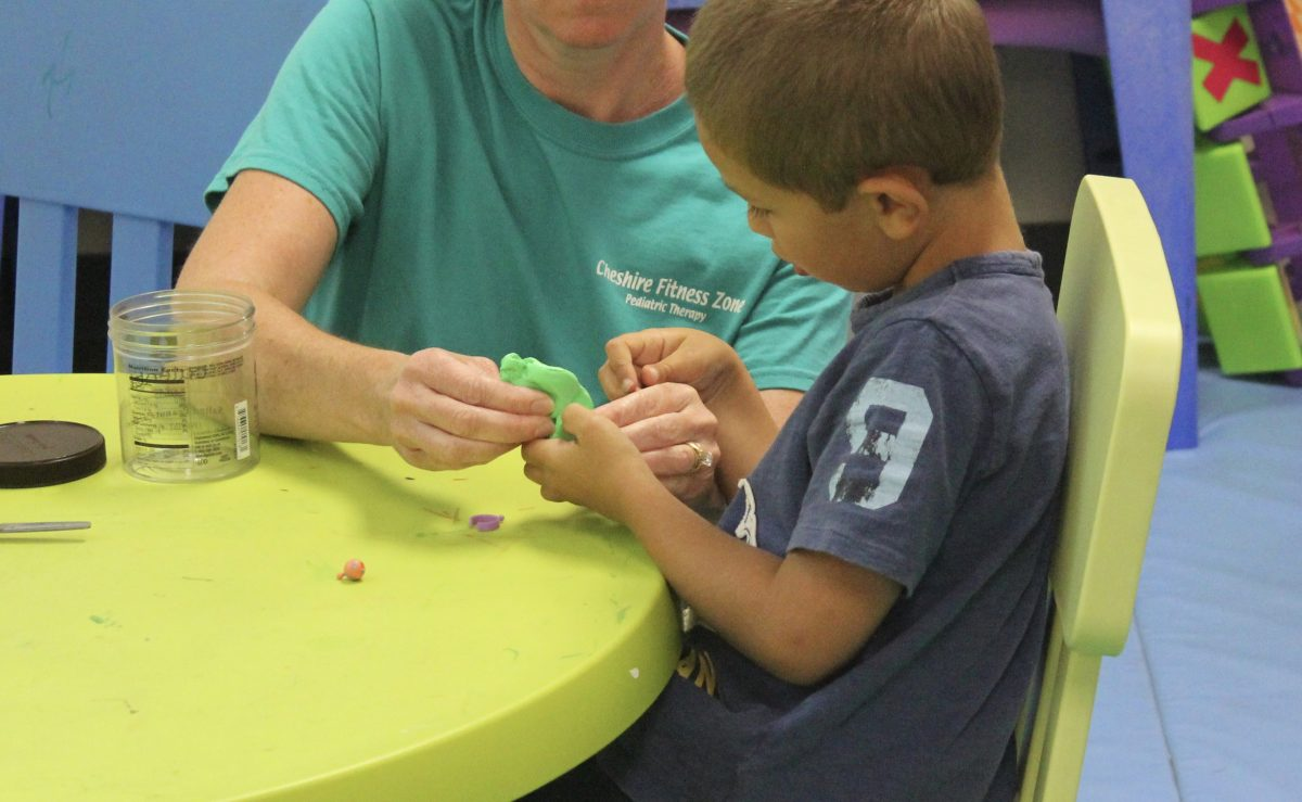 occupational therapist using play doh to treat child