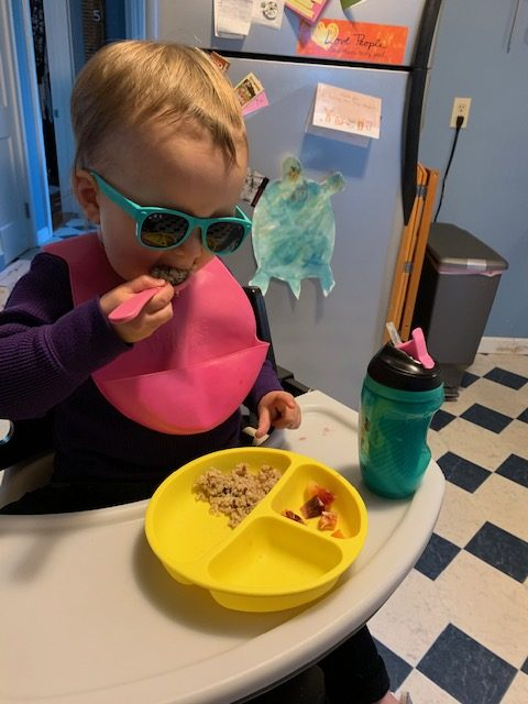 Toddler feeding herself with short spoon