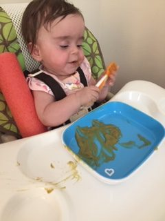 Infant positioned in high chair while being fed