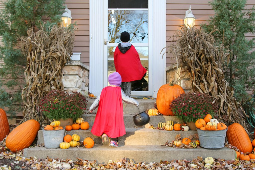 Two young children dressed up in capes for Halloween going trick-or-treating while it is still light out.