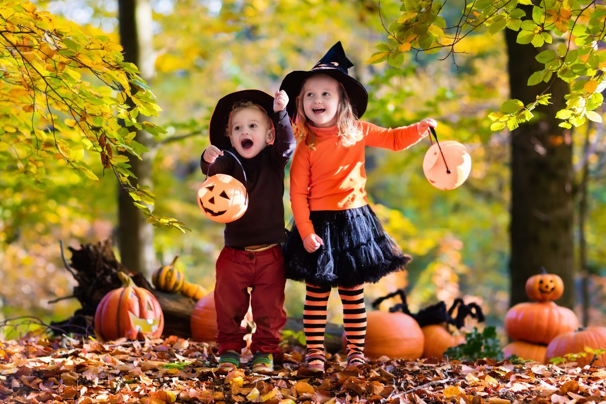 Children having fun partaking in Halloween activities. They are wearing costumes and going trick-or-treating.