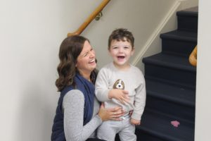 woman laughing with child on stairs