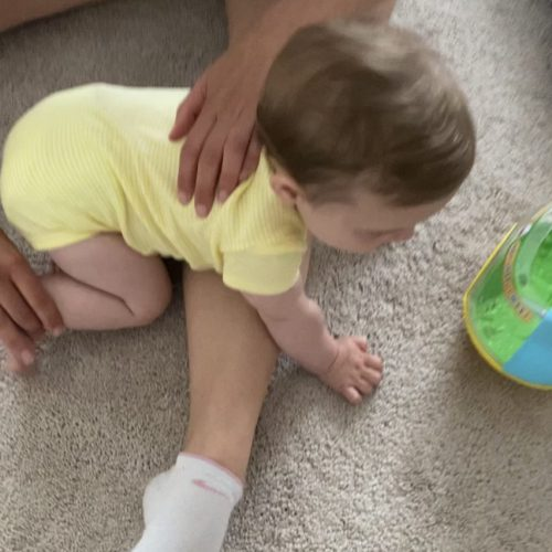 Baby crawling over leg