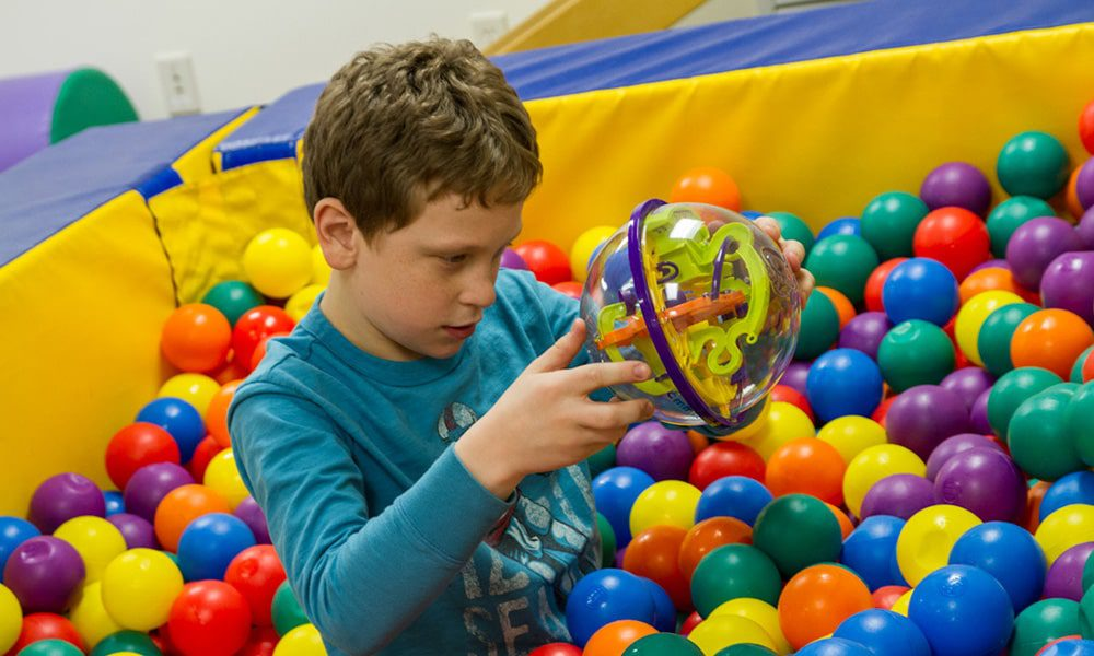 young boy playing with toys in ball pit