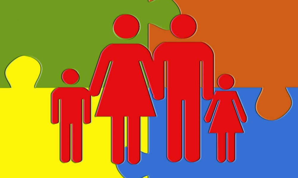a silhouette of a family with puzzle pieces in the background