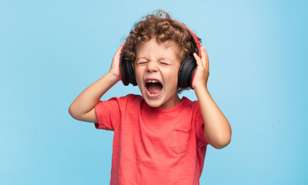 boy wearing headphones listening to loud music